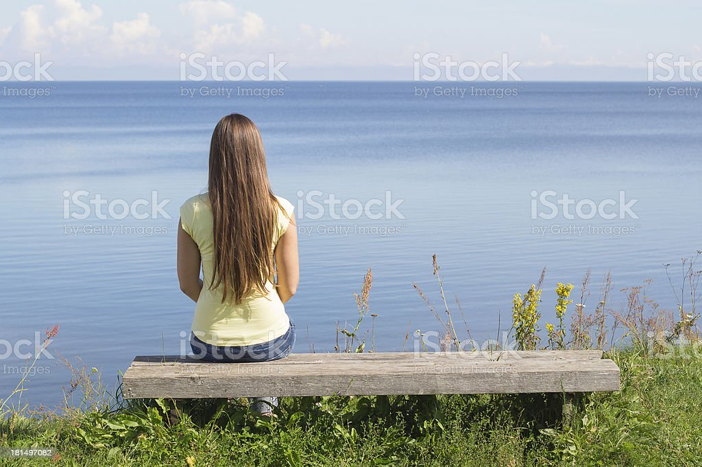 Young woman sitting on bench facing the sea stock photo