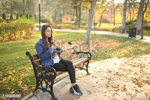 young woman sitting on bench in autumn park and writing message on phone
