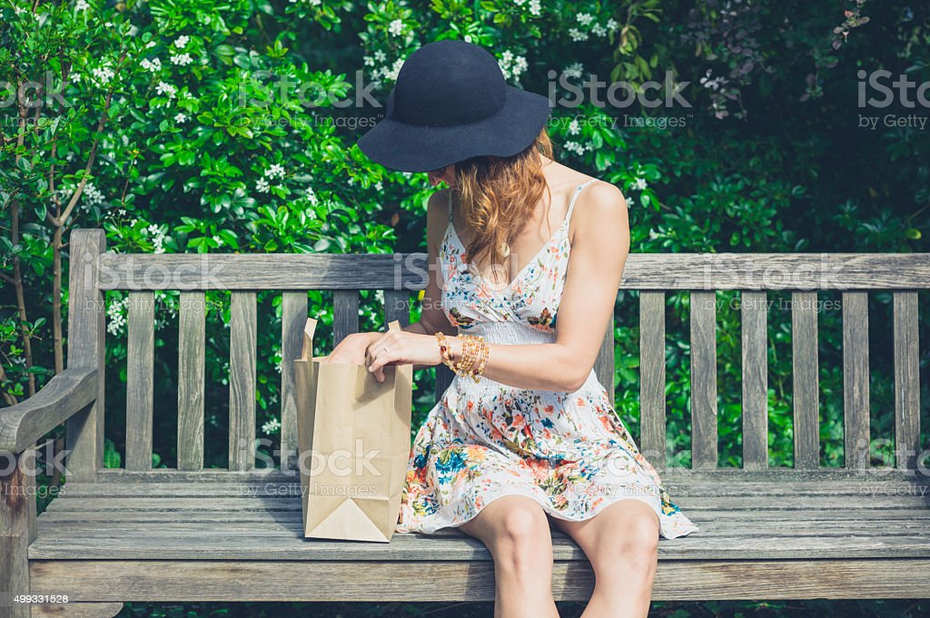 Young woman sitting on bench with paper bag stock photo