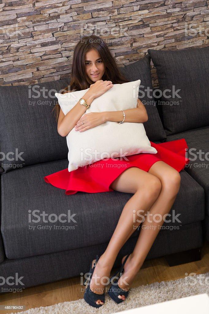 Jovem mulher sentada no sofá preto abraçando almofada branca - foto de acervo