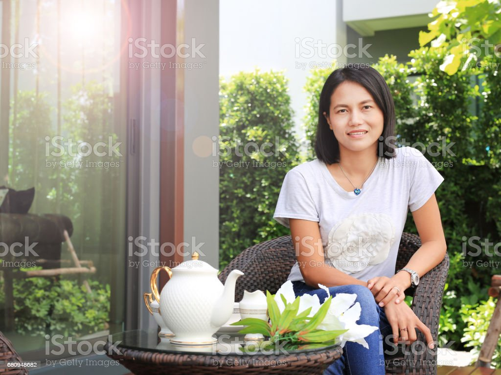Young woman sitting on chair and Tea set on rattan Furniture in the garden. royalty-free stock photo