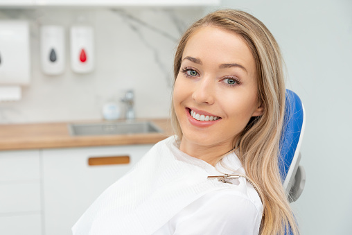 Young smiling woman sitting on chair at dentist office. Dental care, healthy teeth.