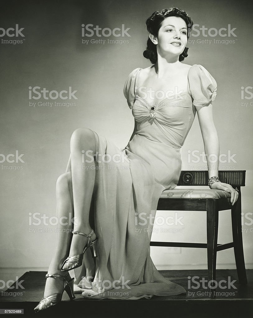 Young woman sitting on chair, posing, (B&W) stock photo