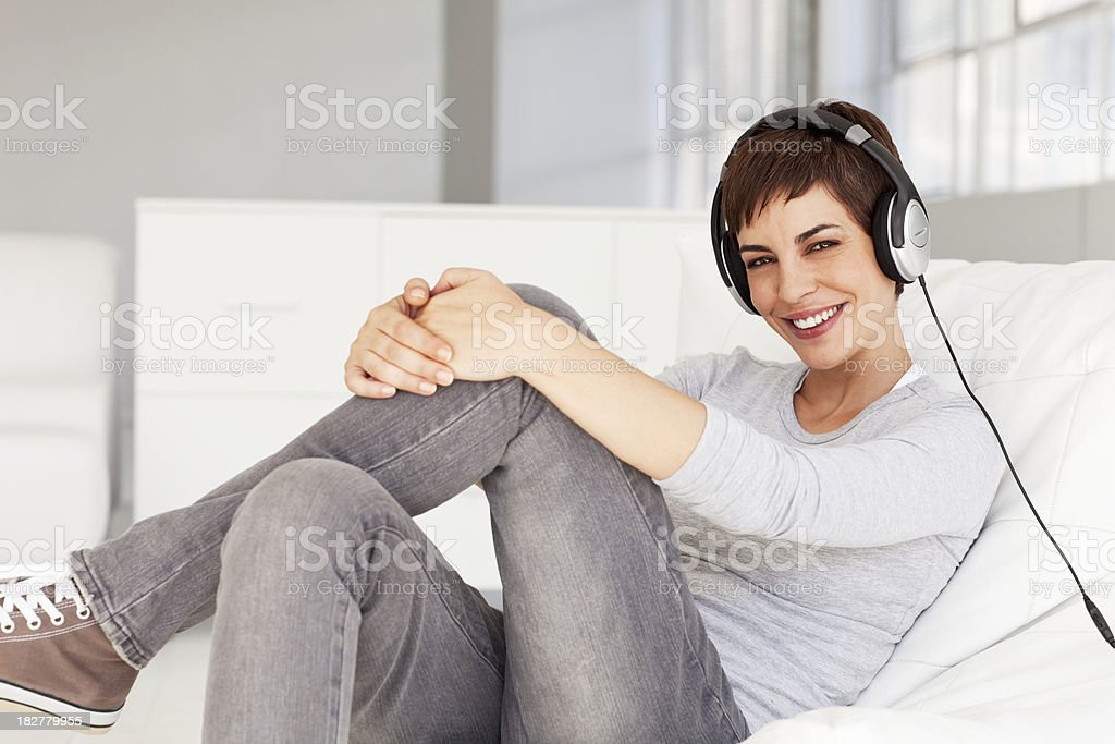 Young Woman Sitting on Chair Smiling Wearing Headphones royalty-free stock photo