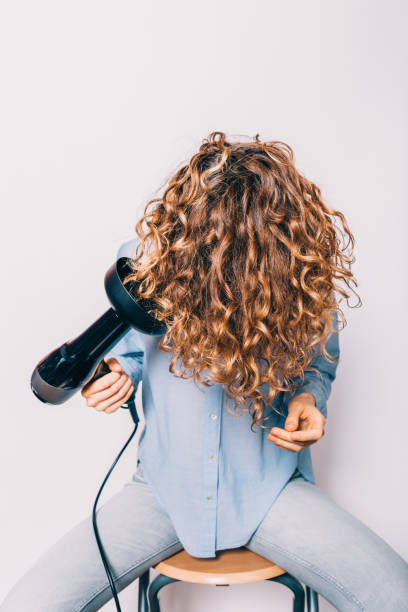 Young woman sitting on chair styling Young woman sitting on chair styling her curly hair with hairdryer with special diffuser nozzle. curly hair stock pictures, royalty-free photos & images
