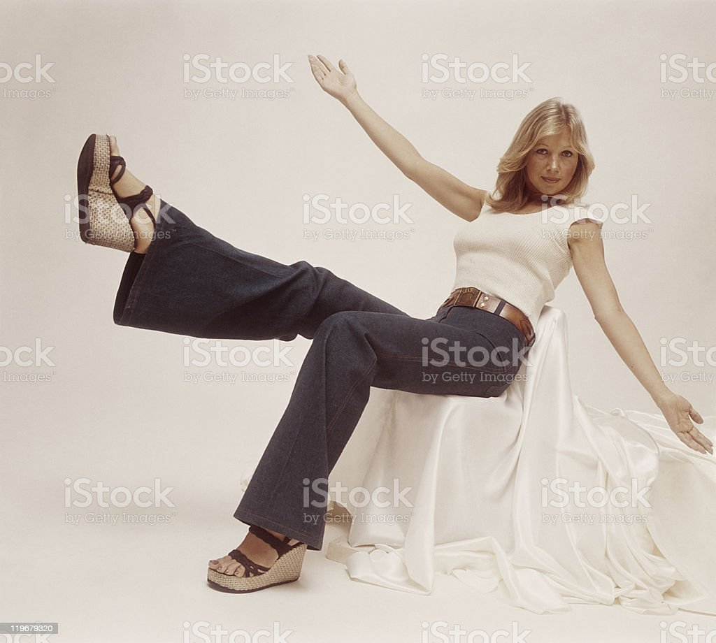 Young woman sitting on chair with arms outstretched, portrait stock photo