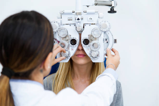 young woman sitting on chair with beautiful optician standing while doing eye test in ophthalmology clinic. - optometrist stock pictures, royalty-free photos & images