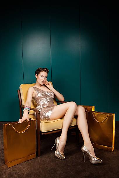 junge frau sitzend auf stuhl mit einkaufstaschen - schuhe auf englisch stock-fotos und bilder