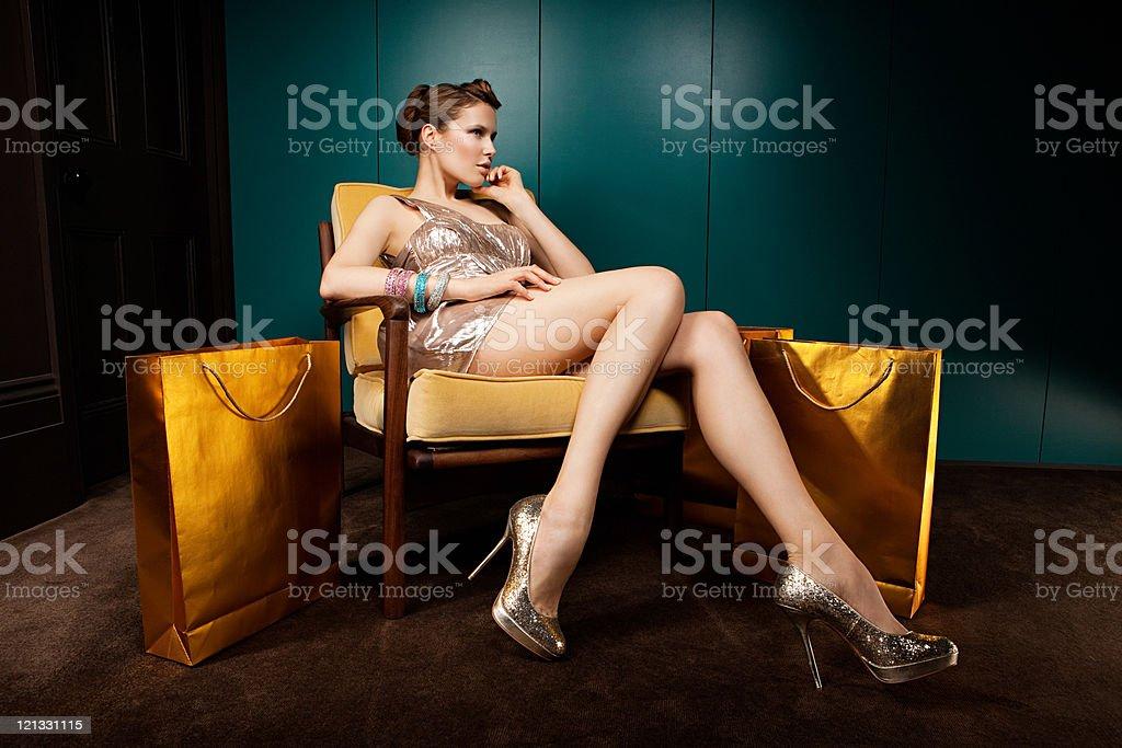 Jovem mulher sentada na cadeira com sacos de compras - foto de acervo