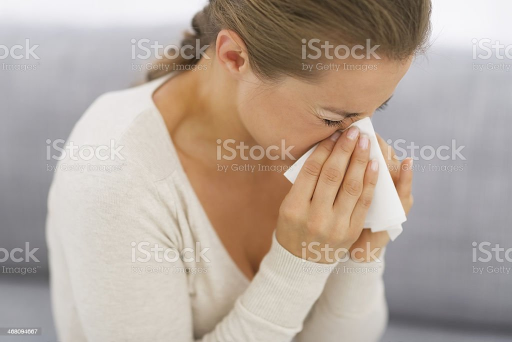 young woman sitting on couch and blowing nose stock photo