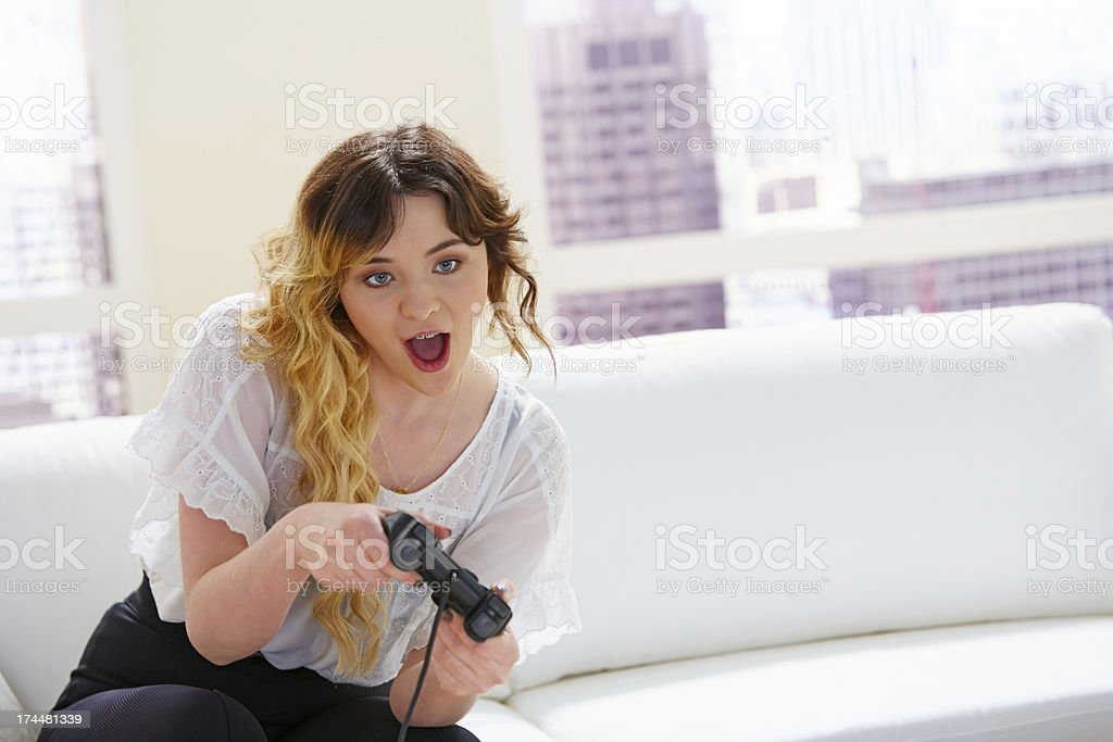 Young woman sitting on couch playing exciting video game stock photo