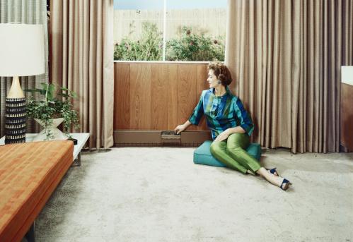 Young woman sitting on cushion adjusting radiator's knob