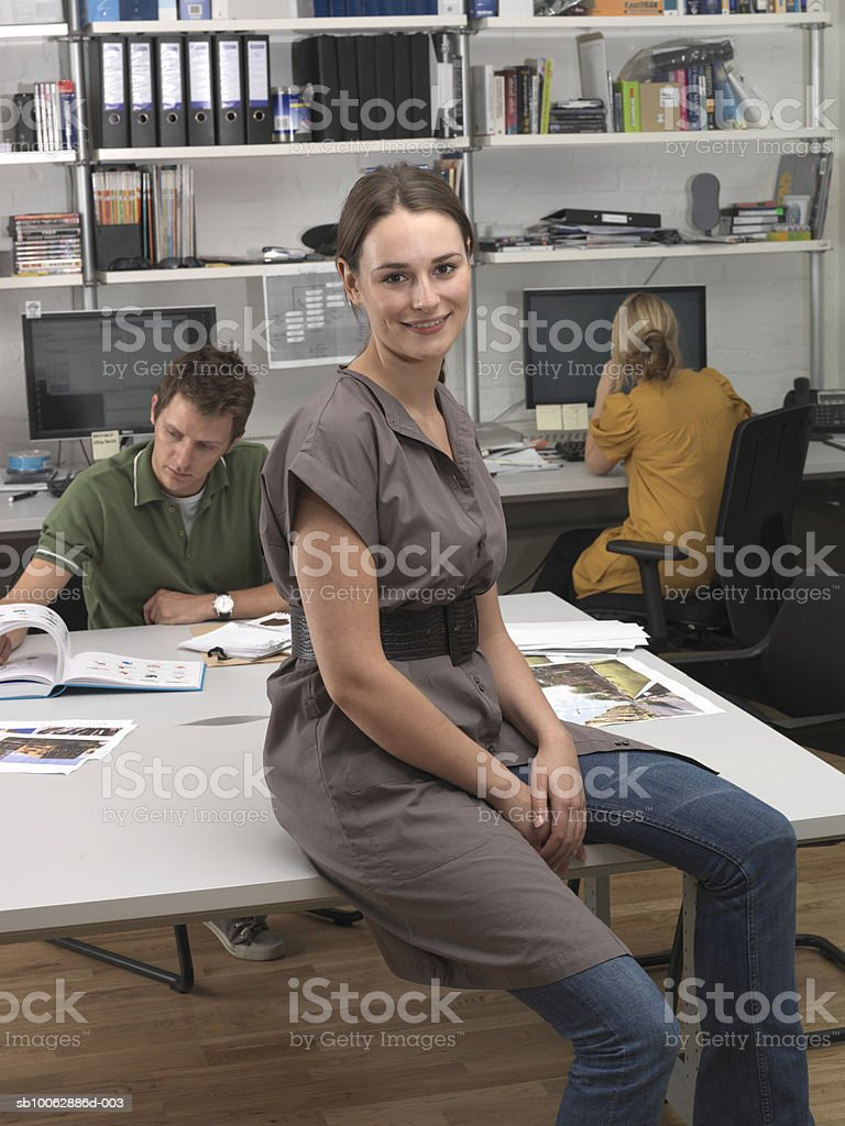 Young woman sitting on desk, smiling, colleagues in background foto de stock libre de derechos