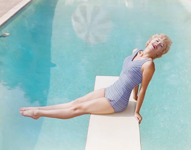 młoda kobieta siedzi na platforma do skoków do wody, uśmiech, portret - archiwalny zdjęcia i obrazy z banku zdjęć