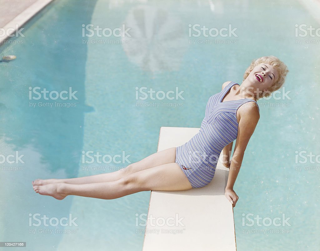 Young woman sitting on diving board, smiling, portrait stock photo