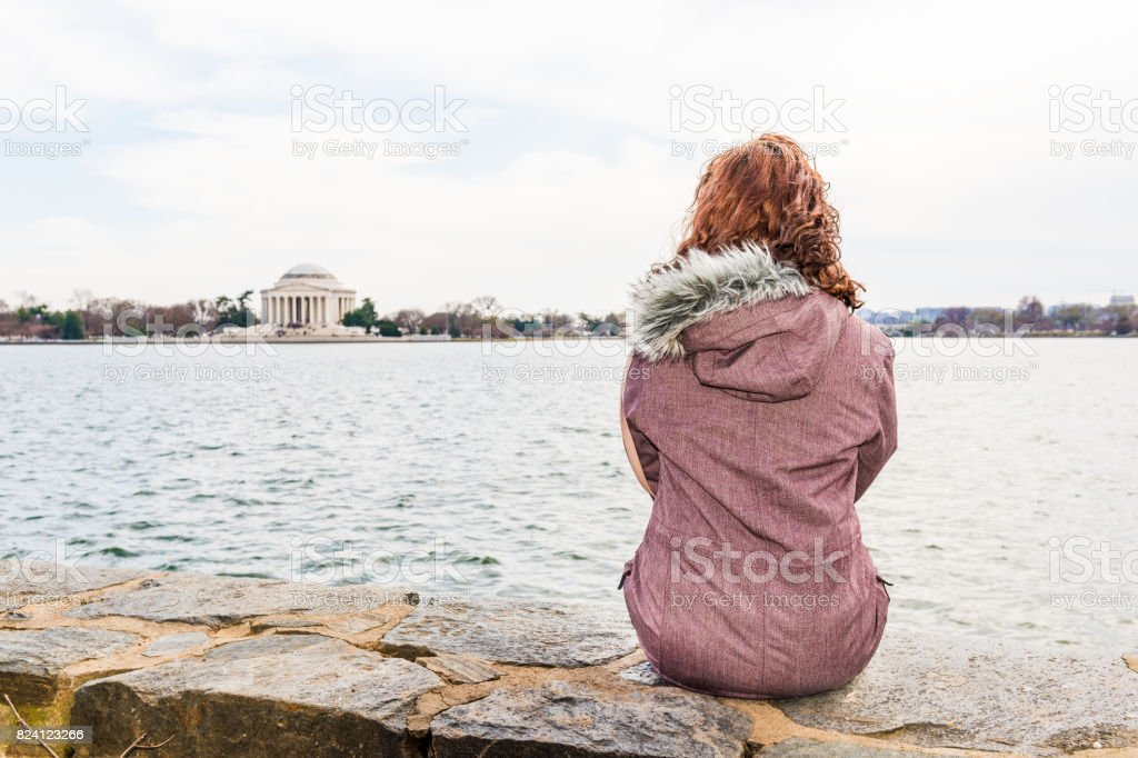 Young woman sitting on edge looking over Tidal Basin and Thomas Jefferson Memorial in park stock photo