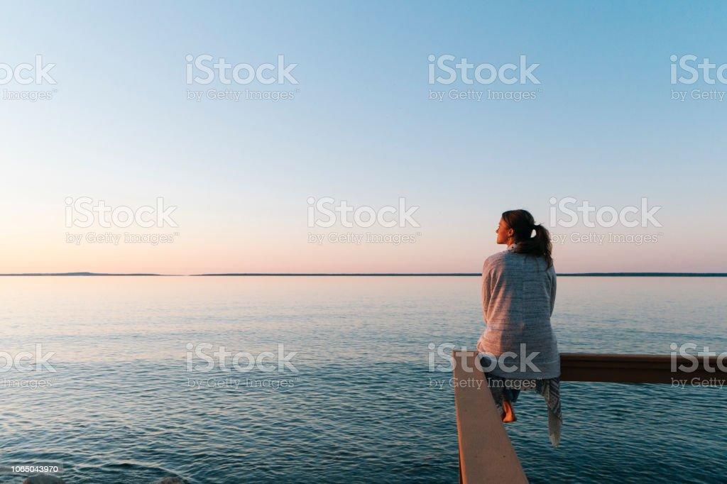 Manzaraya kenarında oturan genç kadın bakıyor - Royalty-free 30-34 Yaş Stok görsel