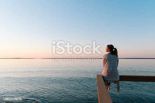 istock Young woman sitting on edge looks out at view 1065043970