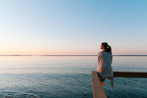 Young woman sitting on edge looks out at view sunset and sea behind, Michigan tuinkers stock pictures, royalty-free photos & images
