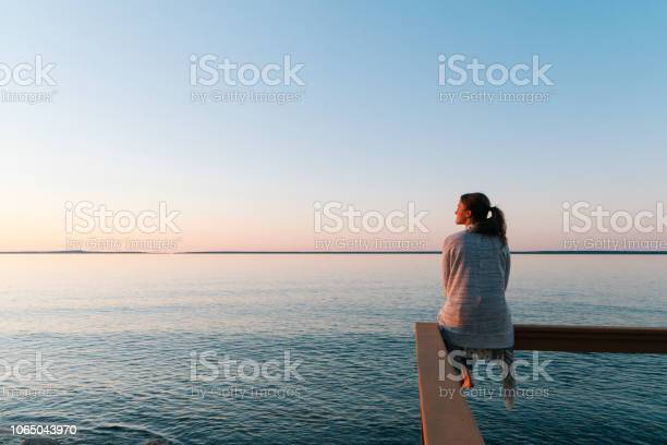 Photo of Young woman sitting on edge looks out at view