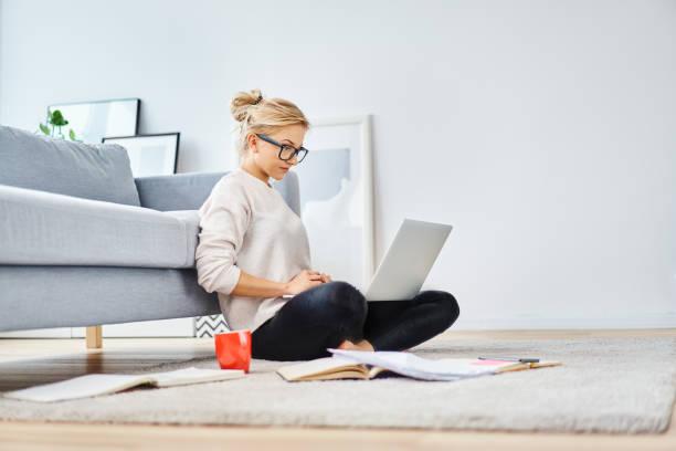 Junge Frau sitzt im Stock zu Hause arbeiten mit Notebook und Unterlagen – Foto