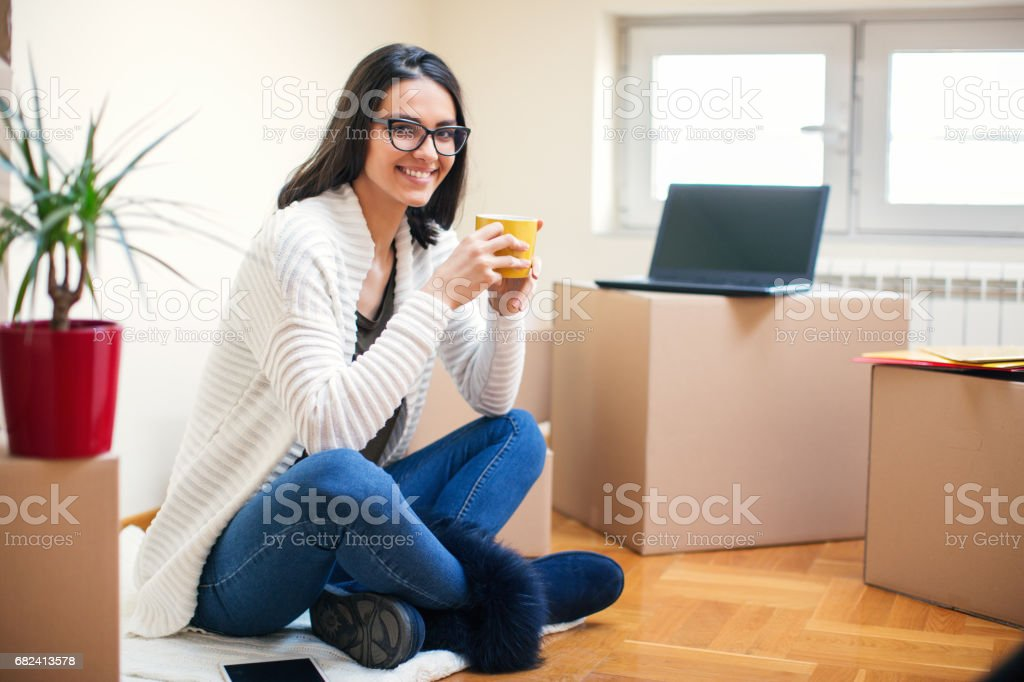 Young woman sitting on floor in new apartment royalty-free stock photo