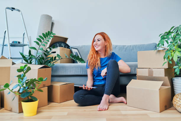 Young woman sitting on floor in new apartment with tablet and looking away stock photo