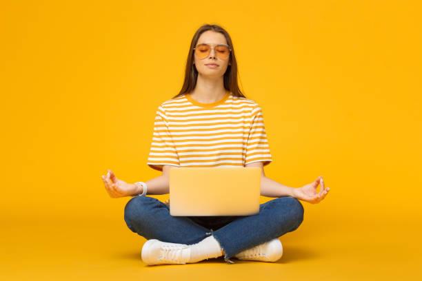 mulher nova que senta-se no assoalho com o portátil que meditando no pose dos lótus da ioga isolado no fundo amarelo - membro parte do corpo - fotografias e filmes do acervo