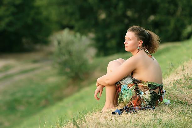 Junge Frau sitzt auf Gras – Foto