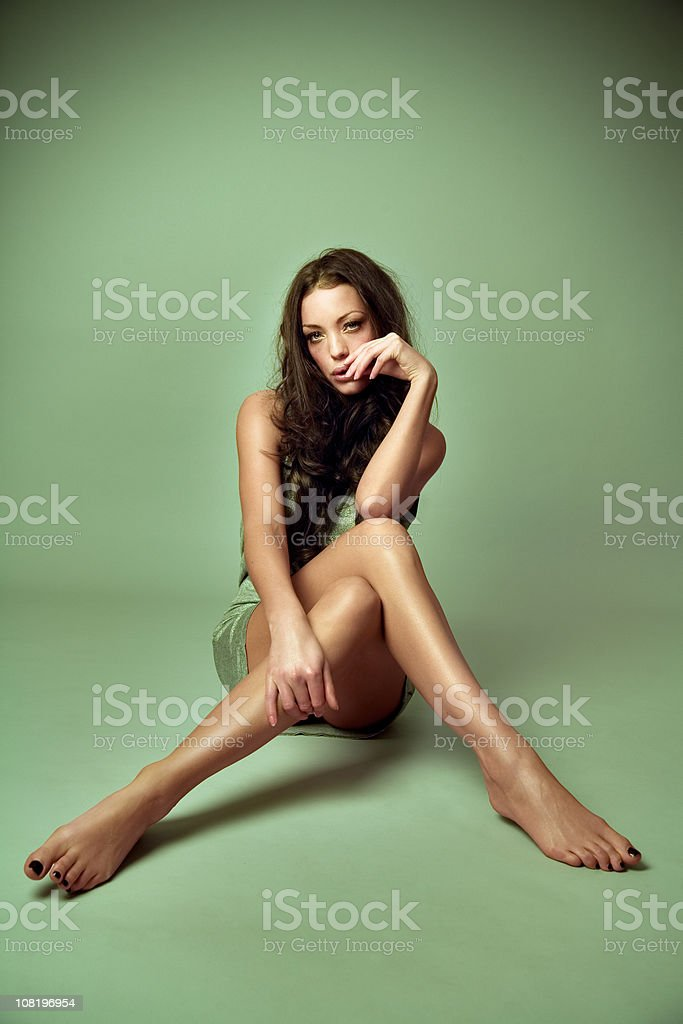 Young Woman Sitting on Green Background royalty-free stock photo