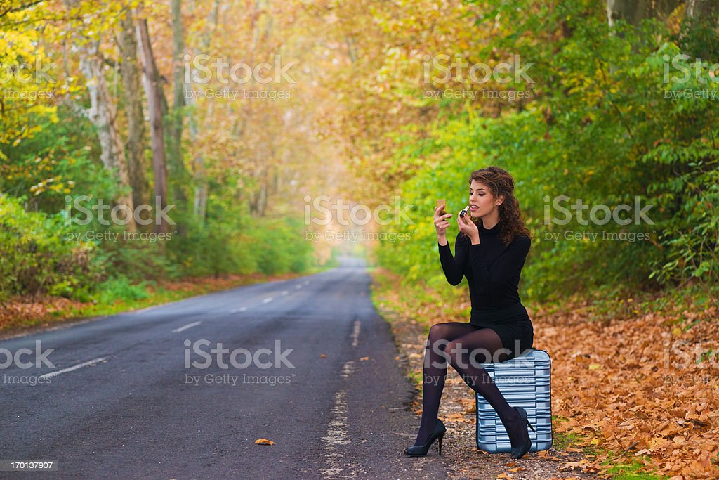 Young woman sitting on her suitcase and applying makeup stock photo