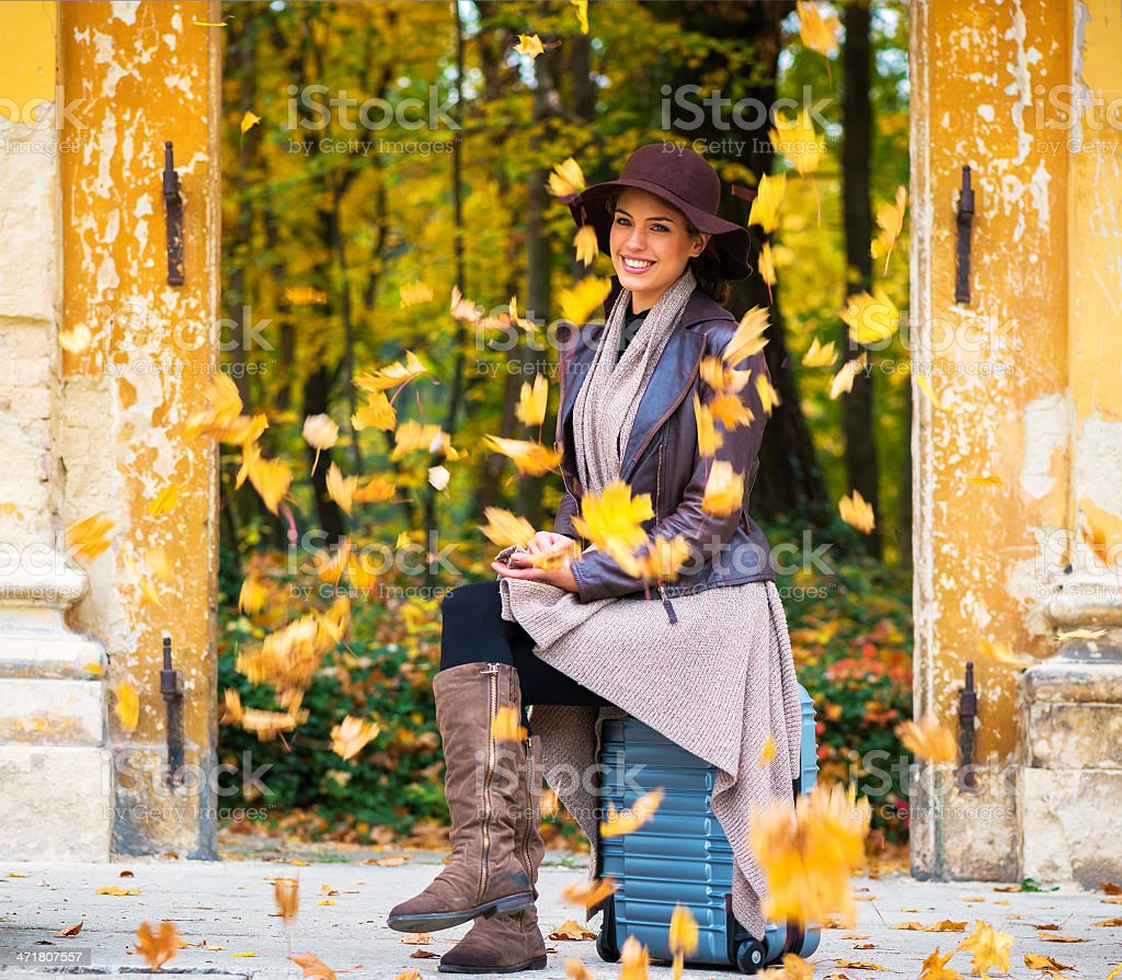 Young woman sitting on her suitcase royalty-free stock photo