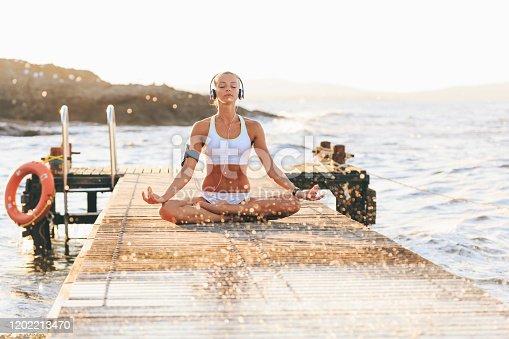 Woman sitting legs crossed on pier, meditating i lotus position.