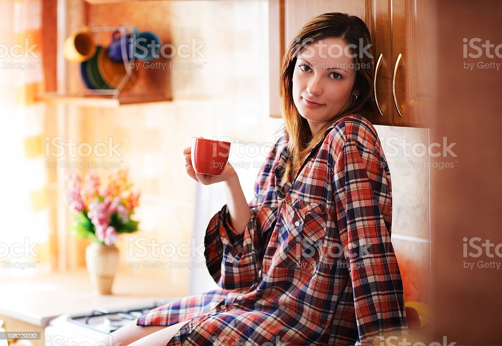 Young Woman Sitting on Kitchen Counter Holding Tea Cup royalty-free stock photo