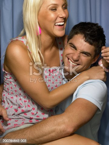 621502402 istock photo Young woman sitting on man's lap in photo booth 200284843-003