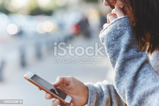 istock Young woman sitting on near street door and uses smartphone 1053400818