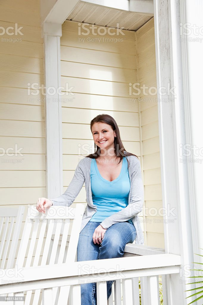 Young woman sitting on porch stock photo