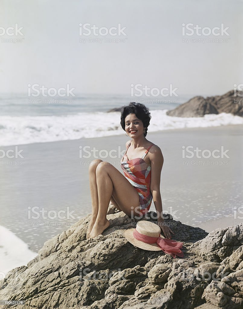 Young woman sitting on rock beside sea, smiling, portrait stock photo