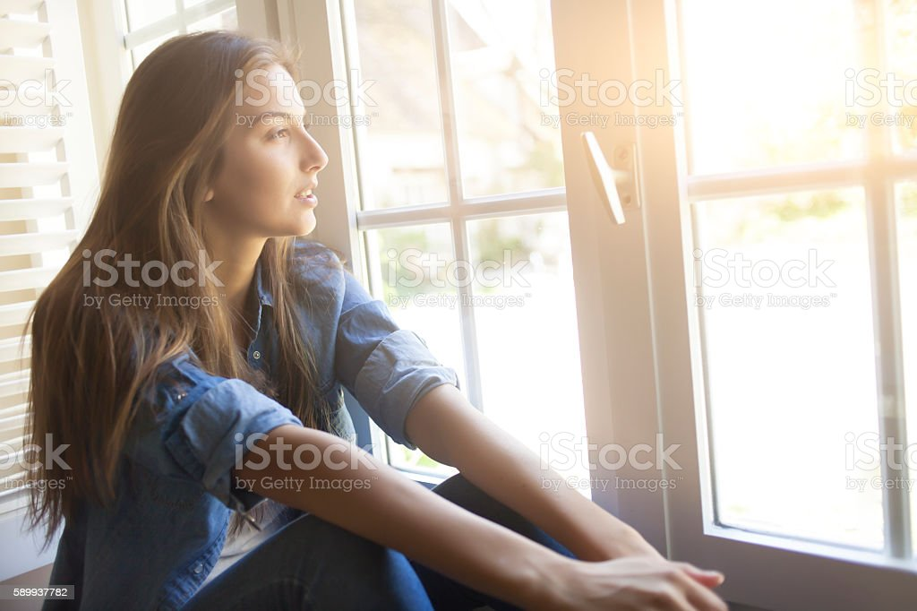 Young woman sitting on window\'s sill and looking outdoors. With long...