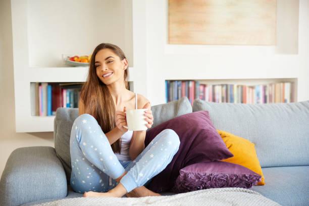 Junge Frau sitzt auf dem Sofa und genießen ihren Kaffee am Morgen zu Hause – Foto