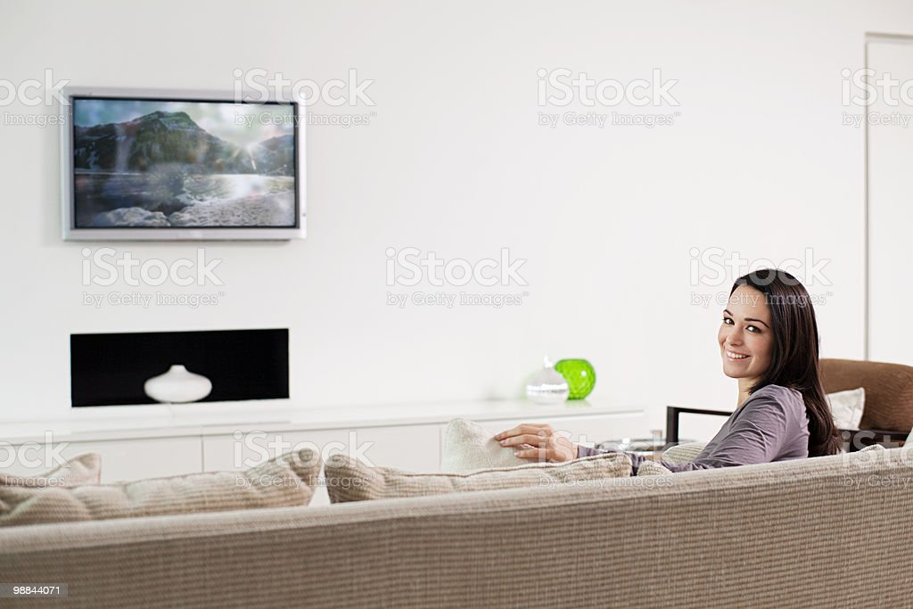 Young woman sitting on sofa royalty free stockfoto