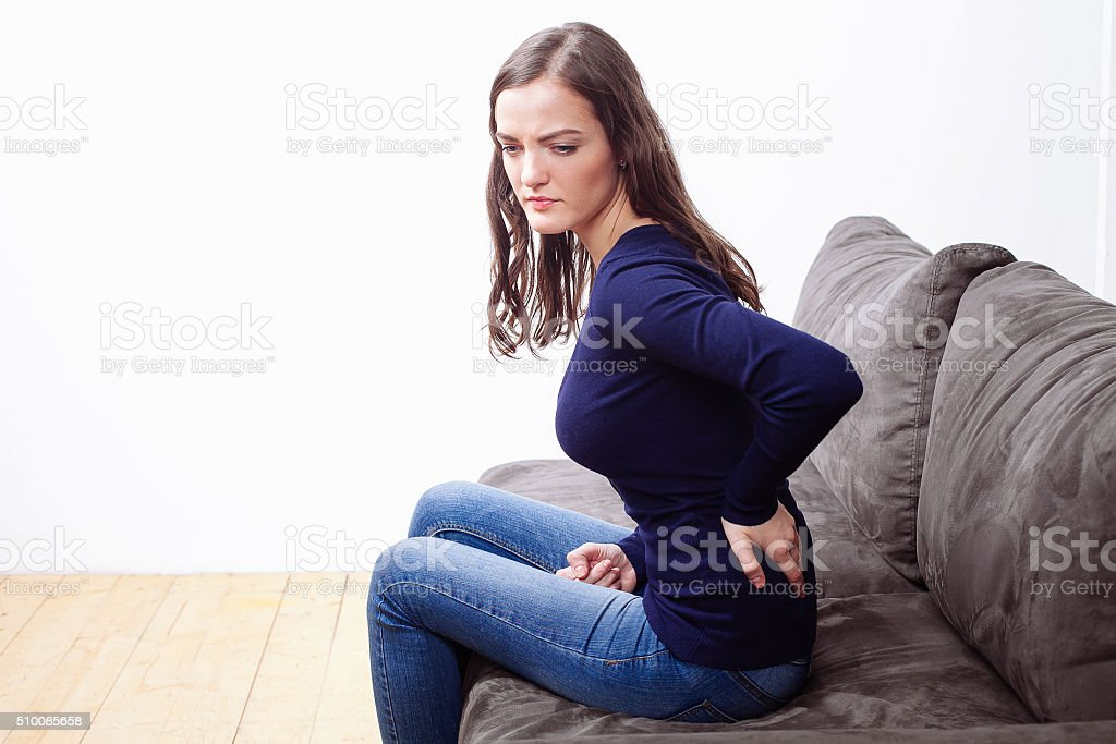 Young Woman Sitting On Sofa Suffering From Ache stock photo