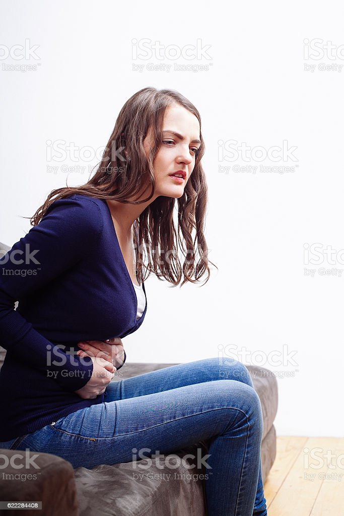Young Woman Sitting On Sofa Suffering From stomach ache stock photo