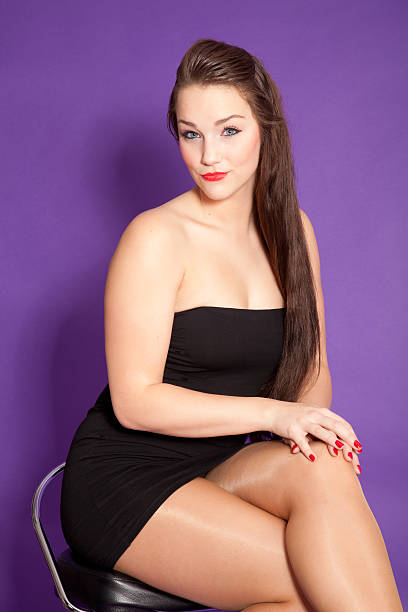 young woman sitting on stool - mini dress stock photos and pictures
