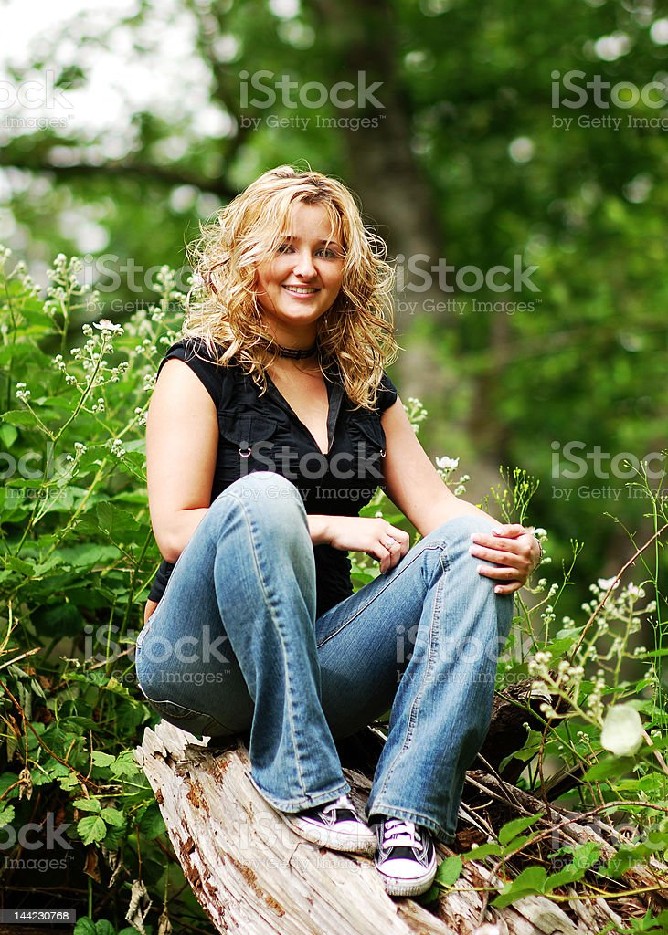 Young woman sitting on stump royalty-free stock photo