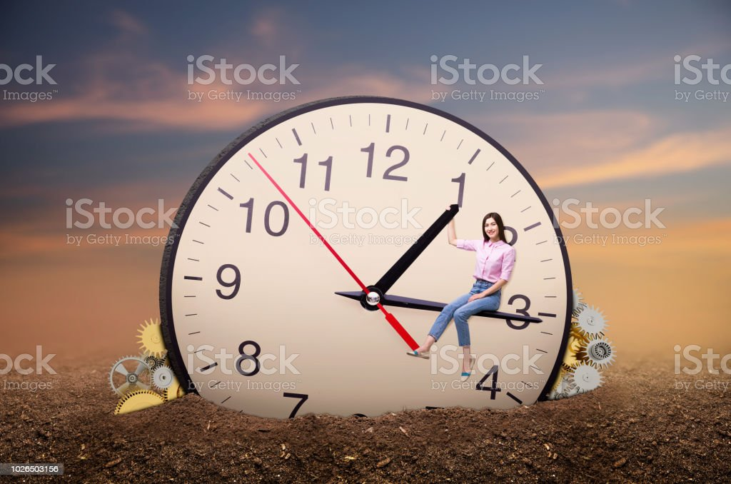 Young woman sitting on the arrow of a huge clock stock photo
