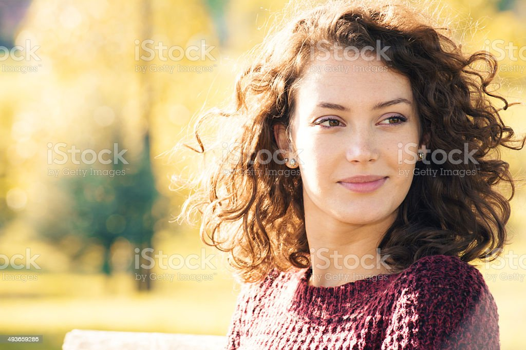 Young woman sitting on the bench at autumn stock photo