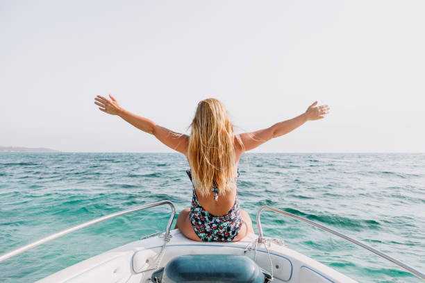 Young woman sitting on the bow of the boat enjoying the view at the sea stock photo