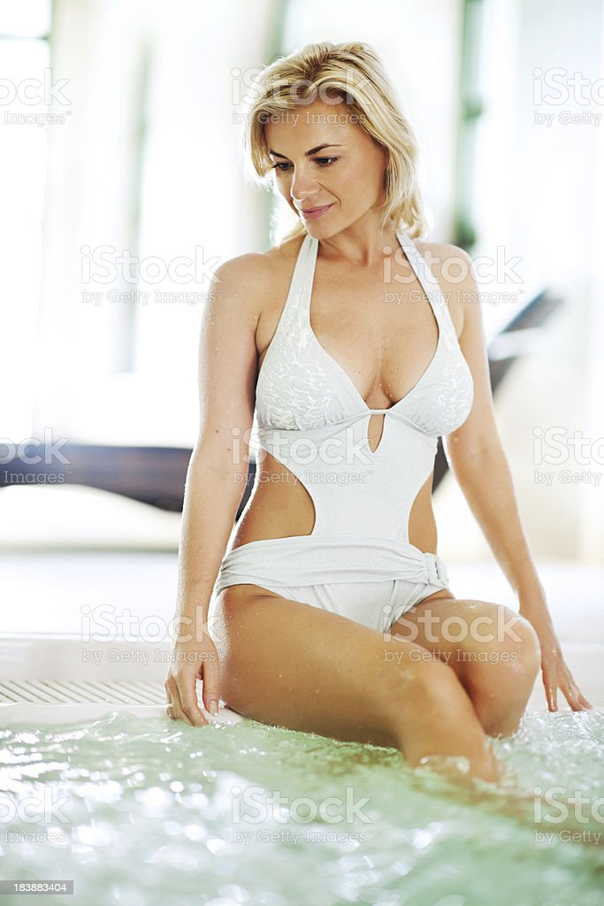 Young woman sitting on the edge of a Jacuzzi. royalty-free stock photo