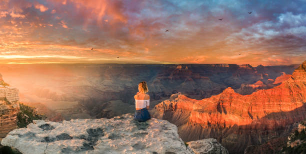 Young woman sitting on the edge of rim and enjoying the panoramic view of Grand Canyon stock photo